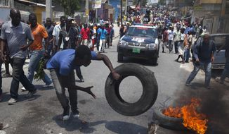 A protester burns tires on the street during a protest against President Michel Martelly's government in Port-au-Prince, Haiti, Tuesday April 15, 2014. Those demonstrating called for the resignation of  Martelly.( AP Photo/Dieu Nalio Chery)