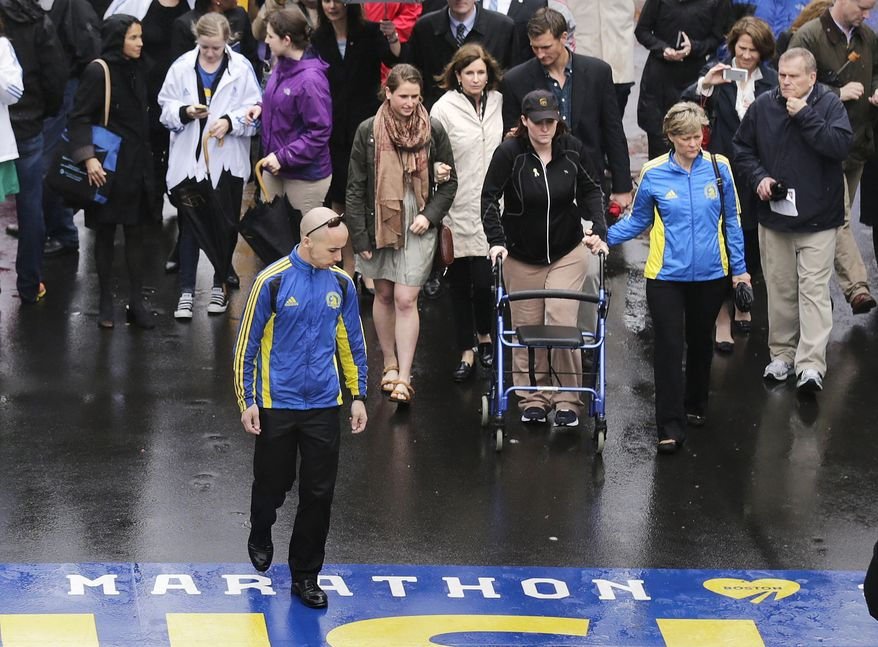 Marathon survivor Erika Brannick, a teacher from Maryland, uses a walker as she prepares to cross the finish line following a tribute in honor of the one year anniversary of the Boston Marathon bombings, Tuesday, April 15, 2014 in Boston. (AP Photo/Charles Krupa)