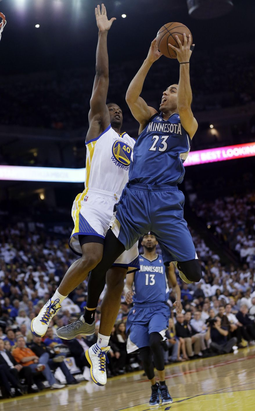 Minnesota Timberwolves' Kevin Martin (23), right, drives to the basket as Golden State Warriors' Harrison Barnes (40) defends during the first half of an NBA basketball game on Monday, April 14, 2014, in Oakland, Calif. (AP Photo/Marcio Jose Sanchez)
