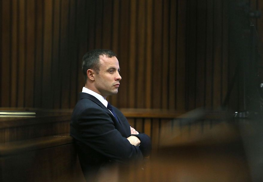 Oscar Pistorius listens to evidence being given in court in Pretoria, South Africa, Tuesday, April 15, 2014 after questioning by state prosecutor Gerrie Nel, had earlier finished. Pistorius is charged with the murder of his girlfriend Reeva Steenkamp, on Valentines Day in 2013. (AP Photo/Alon Skuy, Pool)