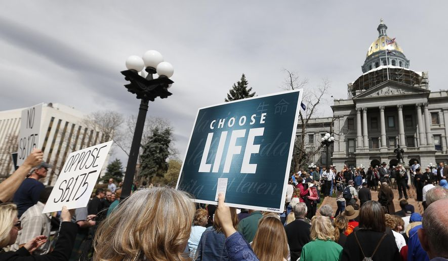 Demonstrators rally against Colorado Senate Bill 175, in a protest led by Archbishop of Denver Samuel J. Aquila, on the steps of the state capitol in Denver, Tuesday, April 15, 2014. The bill up for debate Tuesday is described as a guarantee that state or local policies won't interfere with reproductive decisions such as abortion and contraception. Democratic sponsors say the measure is needed to protect women's rights. (AP Photo/Brennan Linsley)