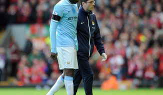 Manchester City's Yaya Toure, left, leaves the field after sustaining an injury during their English Premier League soccer match against Liverpool at Anfield in Liverpool, England, Sunday April. 13, 2014. (AP Photo/Clint Hughes)