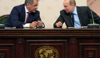 Russian President Vladimir Putin, right, and Defense Minister and Russian Geographical Society Head Sergei Shoigu attend a meeting of a board of trustees of the Russian Geographical Society in a library of Moscow State University in Moscow, Russia, Tuesday, April 15, 2014. (AP Photo/RIA-Novosti, Alexei Druzhinin, Presidential Press Service)