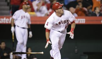 Los Angeles Angels' Mike Trout watches his game-tying two-run home run during the ninth inning of a baseball game against the Oakland Athletics on Tuesday, April 15, 2014, in Anaheim, Calif. (AP Photo/Jae C. Hong)