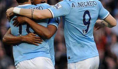 Manchester City's Fernandinho, centre, celebrates with Sergio Aguero, left and Alvaro Negredo after scoring against Sunderland during the English Premier League soccer match between Manchester City and Sunderland at The Etihad Stadium, Manchester, England, Wednesday, April  16, 2014. (AP Photo/Rui Vieira)