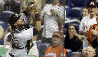 Miami Marlins catcher Jarrod Saltalamacchia can't come up with the ball on a foul hit by Anthony Rendon during the sixth inning of a baseball game, Wednesday, April 16, 2014, in Miami. (AP Photo/Lynne Sladky)