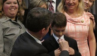 Kansas Gov. Sam Brownback adjusts 8-year-old Brad Eckart's tie before taking a group photo with parents of children with autism who supported a new law requiring limited health insurance coverage for treatment, Wednesday, April 16, 2014, in Overland Park. Brad's mother, to his right, Heidi Eckart, estimates the family has spent $500,000 on treating him. (AP Photo/John Hanna)