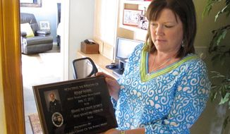 In this April 9, 2014 photo Holly Harris holds a plaque honoring her husband, Dallas Fire-Rescue Capt. Kenneth Luckey Harris, in her home outside West, Texas, on Tuesday, April 9, 2014. Kenneth Harris was one of 15 people killed in a deadly explosion at West Fertilizer Co., that still raises questions in the community one year later about what happened. (AP Photo/Nomaan Merchant)