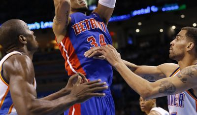 Detroit Pistons guard Peyton Siva (34) shoots between Oklahoma City Thunder forward Serge Ibaka (9) and guard Thabo Sefolosha (25) during the second quarter of an NBA basketball game in Oklahoma City, Wednesday, April 16, 2014. (AP Photo/Sue Ogrocki)