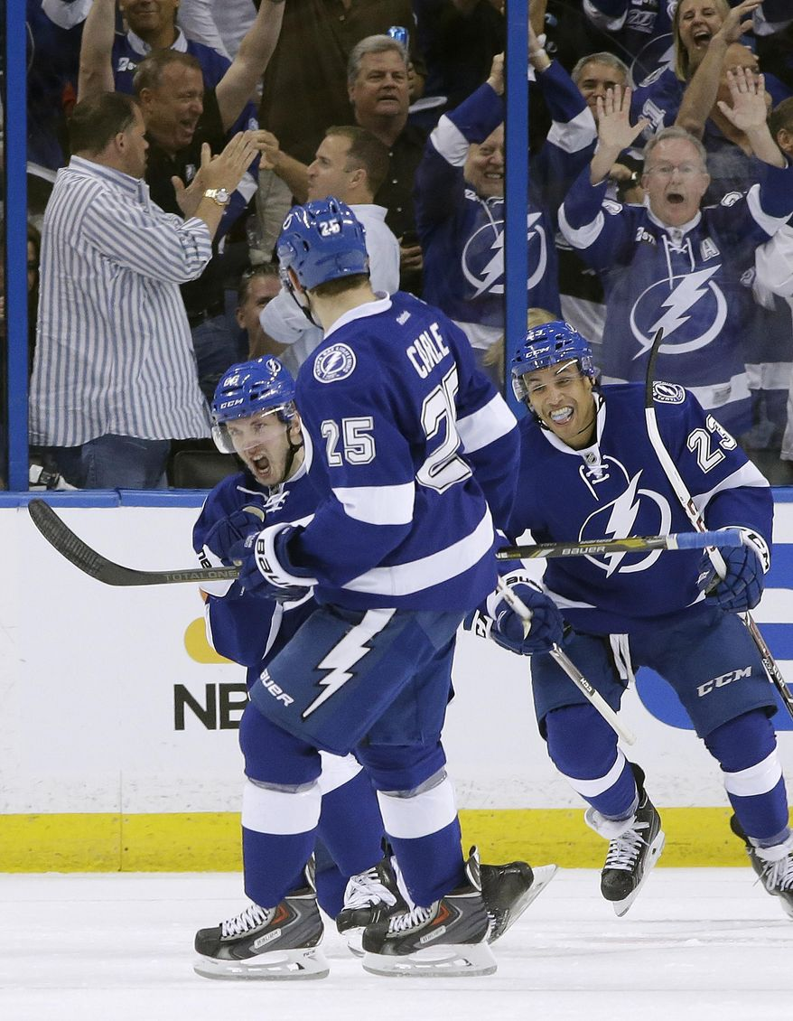 Tampa Bay Lightning right wing Nikita Kucherov (86), of Russia, celebrates with teammates Matt Carle (25) and J.T. Brown after scoring against the Montreal Canadiens during the first period of Game 1 of a first-round NHL hockey playoff series on Wednesday, April 16, 2014, in Tampa, Fla. (AP Photo/Chris O'Meara)