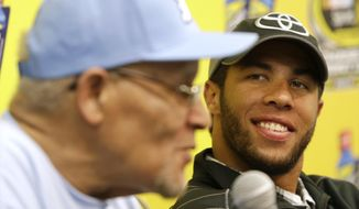 FILE - In this Oct. 27, 2013, file photo, Darrell Wallace Jr., right, winner of Saturday's NASCAR Camping World Truck race, smiles as he listens to Wendell Scott Jr., left, during a news conference at Martinsville Speedway in Martinsville, Va.  Wallace Jr. was the first black driver to win a NASCAR race since the 1960s when he took the checkered flag in a Truck Series race at Martinsville. (AP Photo/Steve Helber, File)
