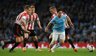Manchester City's Samir Nasri, right, evades Sunderland's Andrea Dossena, left, Jack Colback and Sebastian Larsson during the English Premier League soccer match between Manchester City and Sunderland at The Etihad Stadium, Manchester, England, Wednesday, April 16, 2014. (AP Photo/Rui Vieira)