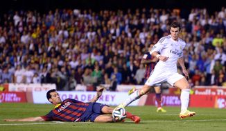 Real's Gareth Bale, right, looses the ball to Barcelona's Sergio Busquets during the final of the Copa del Rey between FC Barcelona and Real Madrid at the Mestalla stadium in Valencia, Spain, Wednesday, April 16, 2014. (AP Photo/Manu Fernandez)
