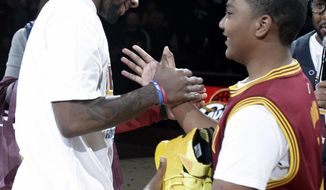 Cleveland Cavaliers' Kyrie Irving, left,  shakes hands with Cleveland Cavaliers fan Brandon Armstrong after giving Armstrong his game shoes for Fan Appreciation Night after an NBA basketball game against the Brooklyn Nets, Wednesday, April 16, 2014, in Cleveland. The Cavaliers defeated the Nets 114-85. (AP Photo/Tony Dejak)