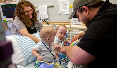 In this Tuesday, April 15, 2014 photo provided by Medical City Children's Hospital in Dallas, Jenni and Dave Ezell visit their twin 9-month-old boys Owen, left, and Emmett, who were born joined at the abdomen. The conjoined twins, separated last summer, were released from the hospital Wednesday and are expected to spend the next three to four weeks in a local inpatient rehabilitation center before being able to go home. (AP Photo/Medical City Children's Hospital)
