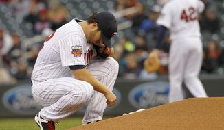 Minnesota Twins pitcher Phil Hughes kneels behind the mound before delivering to the Toronto Blue Jays during the first inning of the MLB American League  baseball game in Minneapolis, Tuesday, April 15, 2014.  (AP Photo/Ann Heisenfelt)