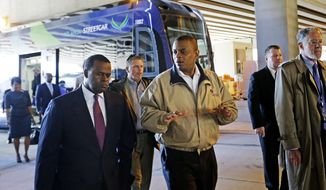 U.S. Secretary of Transportation Anthony Foxx, right, talks with Atlanta Mayor Kasim Reed, left, during a tour of an Atlanta Streetcar, Wednesday, April 16, 2014, in Atlanta. The Department of Transportation said Foxx is traveling around the country to highlight the importance of transportation investment. The first phase of the Atlanta Streetcar is set to open later this year and will run between the Martin Luther King Jr. National Historic Site and Centennial Olympic Park. (AP Photo/David Goldman)