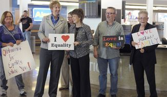Oklahomans for Equality gather at Tulsa International Airport with their signs for a send off celebration in support for the plaintiffs in the Oklahoma Marriage Equality lawsuit as they head to the 10th Circuit Court of Appeals in Denver, Wednesday April 16, 2014. (AP Photo/Brandi Simons)