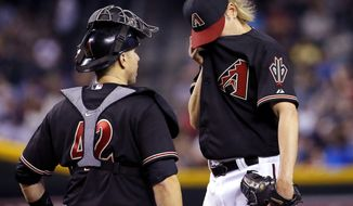 Arizona Diamondbacks pitcher Bronson Arroyo, right, wipes his face as he talks with catcher Miguel Montero during the fourth inning of a baseball game against the New York Mets on Tuesday, April 15, 2014, in Phoenix. (AP Photo/Matt York)