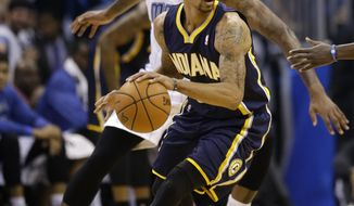 Indiana Pacers' George Hill, front, makes a move to get around Orlando Magic's Kyle O'Quinn during the first half of an NBA basketball game in Orlando, Fla., Wednesday, April 16, 2014. (AP Photo/John Raoux)