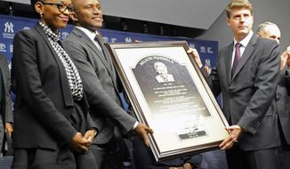 Zondwa Mandela, second from left, his wife Lindo Mandela, left, and New York Yankees owner Hal Steinbrenner, right, pose with a copy of the Nelson Mandela plaque before the Chicago Cubs and the Yankees play Game 2 of a baseball doubleheader on Wednesday, April 16, 2014, at Yankee Stadium in New York. Zondwa is Nelson's grandson. (AP Photo/Bill Kostroun)