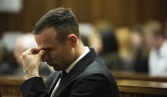 Oscar Pistorius reacts as he  listens to forensic evidence being given in court in Pretoria, South Africa, Wednesday, April 16, 2014.  Pistorius is charged with the murder of his girlfriend, Reeva Steenkamp, on Valentines Day in 2013. (AP Photo/Gianluigi Guercia, Pool)
