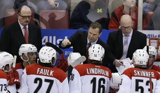 Carolina Hurricanes coach Kirk Muller, center, talks to his team during a timeout in the third period of an NHL hockey game against the Detroit Red Wings in Detroit, Friday, April 11, 2014. The Hurricanes won 2-1. (AP Photo/Carlos Osorio)