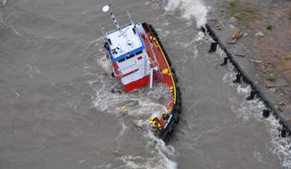 The uninspected towing vessel Todd Michael is grounded on Lake Pontchartrain, Tuesday April 15, 2014. The Coast Guard rescued three crewmembers from the vessel after receiving the report from the UTV Todd Michael. (AP Photo/U.S. Coast Guard Air Station New Orleans)