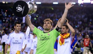 Real goalkeeper Iker Casillas lifts the trophy at the end of the final of the Copa del Rey between FC Barcelona and Real Madrid at the Mestalla stadium in Valencia, Spain, Wednesday, April 16, 2014. Real defeated Barcelona 2-1. (AP Photo/Manu Fernandez)