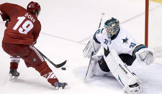 San Jose Sharks' Antti Niemi (31), of Finland, slides over to defend against a shot by Phoenix Coyotes' Shane Doan (19) during the third period of an NHL hockey game Saturday, April 12, 2014, in Glendale, Ariz. The Sharks defeated the Coyotes 3-2. (AP Photo/Ross D. Franklin)