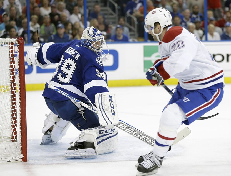 Tampa Bay Lightning goalie Anders Lindback (39), of Sweden, cuts back but cannot stop Montreal Canadiens left wing Thomas Vanek (20), of Austria, from scoring during the third period of Game 1 of a first-round NHL hockey playoff series on Wednesday, April 16, 2014, in Tampa, Fla. (AP Photo/Chris O'Meara)