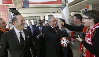 "Atlanta Falcons owner Arthur Blank, center right, high-fives a fan upon arriving for a news conference with Major League Soccer Commissioner Don Garber, left, and Atlanta Mayor Kasim Reed, rear, to announce the city will be getting an MLS expansion team, Wednesday, April 16, 2014, in Atlanta. MLS announced its newest franchise, which will begin play in 2017 at the city's new retractable-roof stadium. The team will be owned by Blank. He donned a traditional soccer scarf and was serenaded by a burgeoning fan group that calls itself ""Terminus Legion,"" a reference to the city's former name. (AP Photo/David Goldman)"