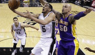 San Antonio Spurs' Cory Joseph (5) is pressured by Los Angeles' Robert Sacre (50) as he tries to score during the second half of an NBA basketball game, Wednesday, April 16, 2014, in San Antonio. Los Angeles won 113-100. (AP Photo/Eric Gay)