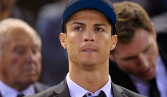 Real's Cristiano Ronaldo waits for the start of  the final of the Copa del Rey between FC Barcelona and Real Madrid at the Mestalla stadium in Valencia, Spain, Wednesday, April 16, 2014. Ronaldo was unable to play due to an injury. (AP Photo/Manu Fernandez)