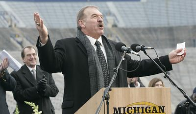 FILe - In this Nov. 21, 2006 file photo, former Michigan football player Dan Dierdorf speaks at a public memorial service for former Michigan football coach Bo Schembechler, with Michigan head coach Lloyd Carr behind him on stage, at Michigan Stadium in Ann Arbor, Mich. Dierdorf is coming back to the booth and will be the radio analyst for University of Michigan football games this fall. The announcement Thursday, April 17, 2014,  was made by Michigan and IMG College, the school's multimedia rights partner. (AP Photo/Tony Ding, File)