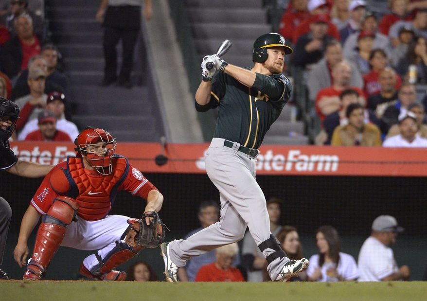 Oakland Athletics' Brandon Moss watches his three-run home run in front of Los Angeles Angels catcher Chris Iannetta during the fourth inning of a baseball game, Wednesday, April 16, 2014, in Anaheim, Calif. (AP Photo/Mark J. Terrill)