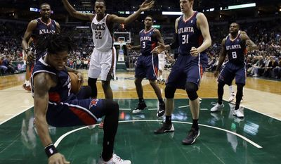 Atlanta Hawks' Cartier Martin, front left, tries to save the ball during the second half of an NBA basketball game against the Milwaukee Bucks, Wednesday, April 16, 2014, in Milwaukee. (AP Photo/Morry Gash)