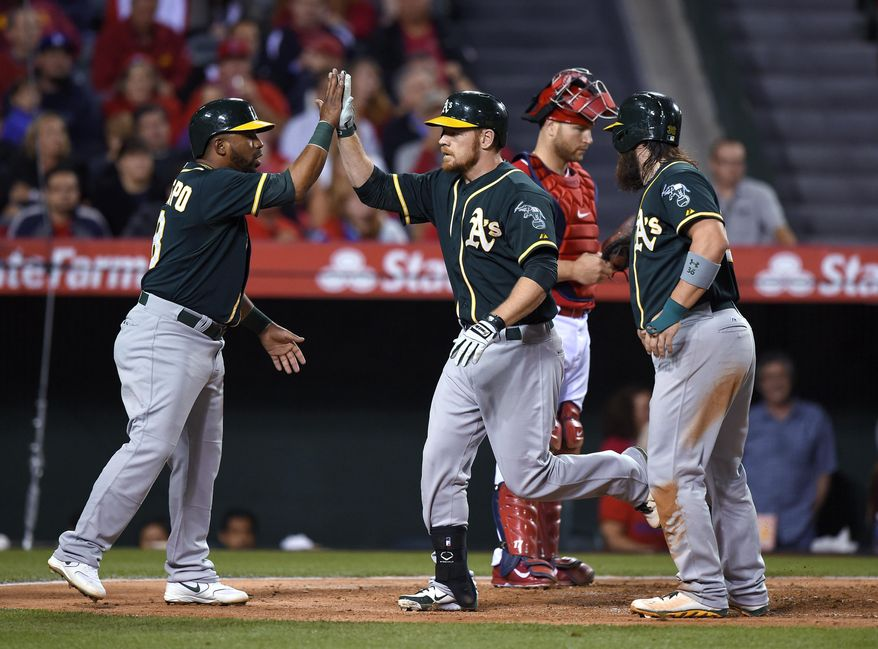 Oakland Athletics' Brandon Moss, second from left, is congratulated by Alberto Callaspo, left, and Derek Norris, right, after hitting a three-run home run, as Los Angeles Angels catcher Chris Iannetta stands behind them during the fourth inning of a baseball game, Wednesday, April 16, 2014, in Anaheim, Calif. (AP Photo/Mark J. Terrill)