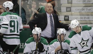 Dallas Stars' Lindy Ruff, center, looks at the scoreboard during the third period in Game 1 of the first-round NHL hockey Stanley Cup playoff series against the Anaheim Ducks on Wednesday, April 16, 2014, in Anaheim, Calif. The Ducks won 4-3. (AP Photo/Jae C. Hong)