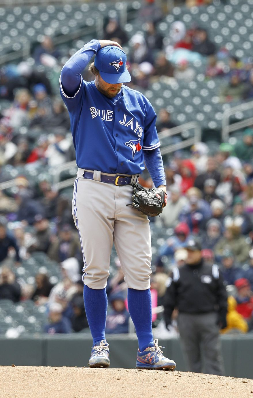 Toronto Blue Jays starting pitcher R.A. Dickey reacts after walking Minnesota Twins' Chris Colabello during the fifth inning of the first baseball game of a doubleheader in Minneapolis, Thursday, April 17, 2014. The Twins won 7-0. (AP Photo/Ann Heisenfelt)