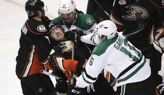 Anaheim Ducks' Stephane Robidas, center, is shoved by Dallas Stars' Ryan Garbutt, right, during the second period in Game 1 of the first-round NHL hockey Stanley Cup playoff series on Wednesday, April 16, 2014, in Anaheim, Calif. (AP Photo/Jae C. Hong)