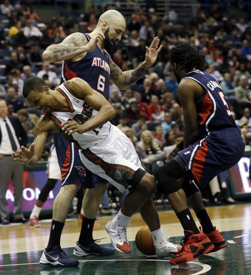 Milwaukee Bucks' Ramon Sessions, front left, loses the ball as he drives between Atlanta Hawks' Pero Antic (6) and DeMarre Carroll (5) during the second half of an NBA basketball game on Wednesday, April 16, 2014, in Milwaukee. (AP Photo/Morry Gash)