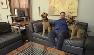 Gordon Wise sits with rescued Airedale terriers in his spacious apartment in an industrial building that was once a meat processing plant. Wise has turned a portion of the building into a haunted house, another portion into a talking board museum and is also in the process of having 16 apartments built inside of the structure. Thursday, April 10, 2014. (AP Photo/San Antonio Express-News,Billy Calzada)