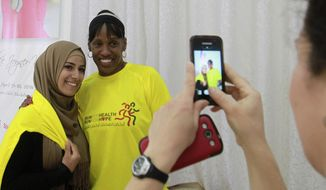 American track and field great Jackie Joyner-Kersee poses with a Palestinian woman in the West Bank city of Ramallah, Thursday , April 17, 2014. The three-time Olympic gold medalist visited the West Bank to encourage Palestinian women to be physically active. (AP Photo/Nasser Shiyoukhi)
