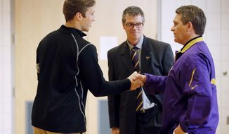 Minnesota State, Mankato defensive back Sam Thompson left, shakes hands with coach Todd Hoffner, as athletic director Kevin Buisman watches on Thursday April 17, 2014, in Mankato , Minn. Players ended their boycott of spring practice and said Thursday they will play for Hoffner, who was reinstated after being exonerated of having child pornography on his cellphone. (AP Photo/Star Tribune, Jerry Holt) ST. PAUL OUT  MINNEAPOLIS-AREA TV OUT  MAGS OUT