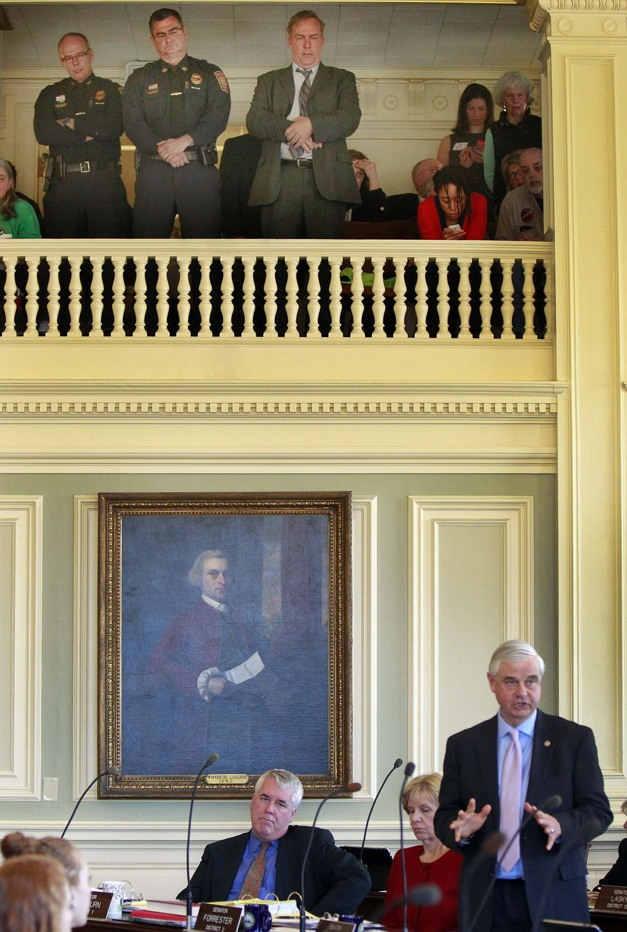 Manchester police officers Nick Willard, left, and Chief Dave Mara, stand next to state Rep. Renny Chushing in the senate gallery as State Sen. Jeb Bradley speaks against a bill to repeal the state's death sentence Thursday April 17, 2014 at the Statehouse in Concord, N.H. Lawmakers voted 12-12, and the tie means that the death penalty will stay on the books. (AP Photo/Jim Cole)