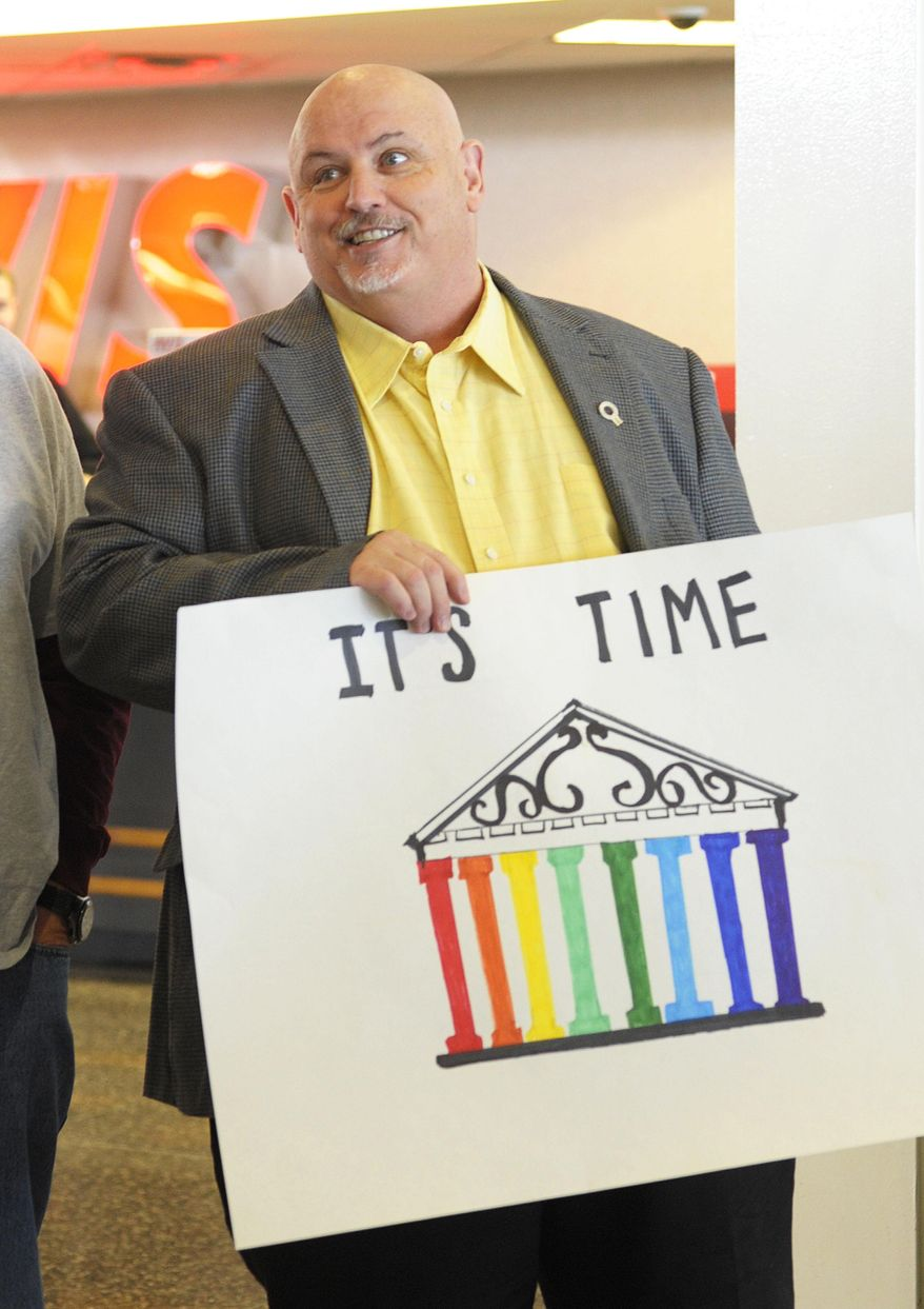 "Toby Jenkins holds an ""It's Time"" sign as Oklahomans for Equality gathered at Tulsa International Airport with their signs for a send off celebration in support for the plaintiffs in the Oklahoma Marriage Equality lawsuit as they head to the 10th Circuit Court of Appeals in Denver Wednesday April 16, 2014. (AP Photo/Brandi Simons)"