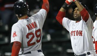 Boston Red Sox's Daniel Nava (29) and Jonathan Herrera celebrate after scoring on a double by Jackie Bradley Jr., off a pitch by Chicago White Sox second baseman Leury Garcia, pitching in relief, during the 14th inning of a baseball game Thursday, April 17, 2014, in Chicago. The Red Sox won 6-4. (AP Photo/Charles Rex Arbogast)