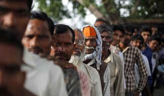 ** FILE ** Indians stand in a queue to cast their votes in Shahbazpur Dor village in Amroha, in the northern Indian state of Uttar Pradesh, Thursday, April 17, 2014. (AP Photo/Altaf Qadri)