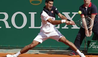 Novak Djokovic of Serbia, returns the ball to Pablo Carreno Busta of Spain during their third round match of the Monte Carlo Tennis Masters tournament in Monaco, Thursday, April 17, 2014. Djokovic won 6-0 6-1. (AP Photo/Michel Euler)